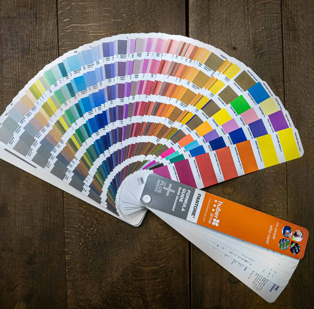Pantone Color Formula Guide Spread Out on Wooden Table