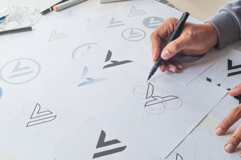 Close Up of Man's Hands Drawing Logo Designs