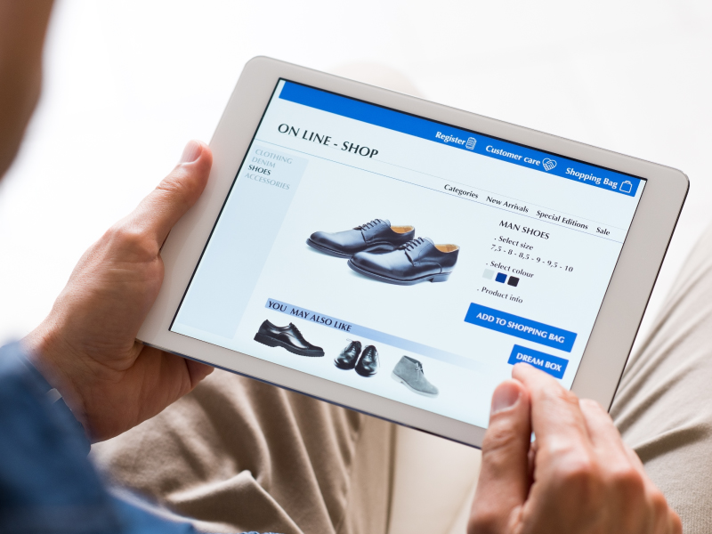 Man Holding White Tablet with Screen Showing Shoe E-Commerce Website
