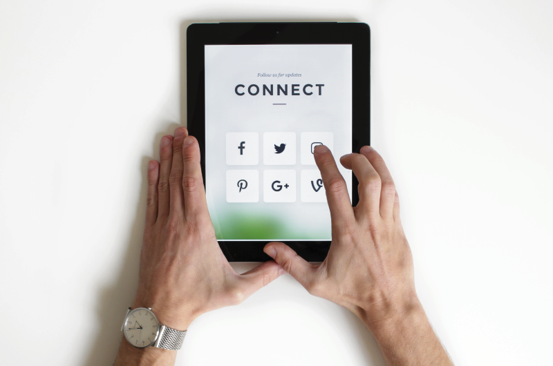 Man's hands holding tablet with social media icons on screen