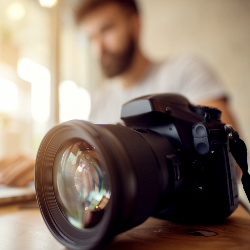 DSLR camera in foreground, blurred male photographer sitting at laptop in background
