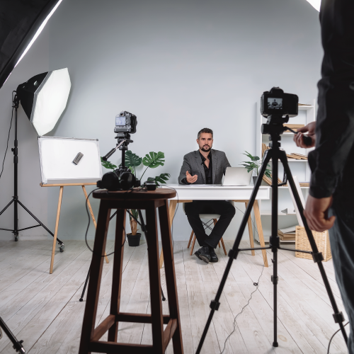 Photographer with camera on tripod in foreground, man posed at a desk for styled photo shoot in background