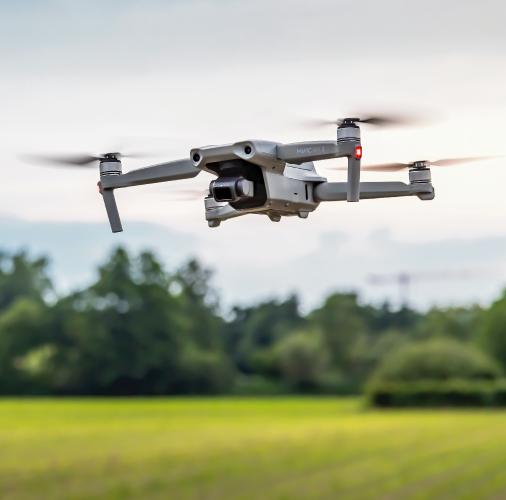 Drone in green field while in flight