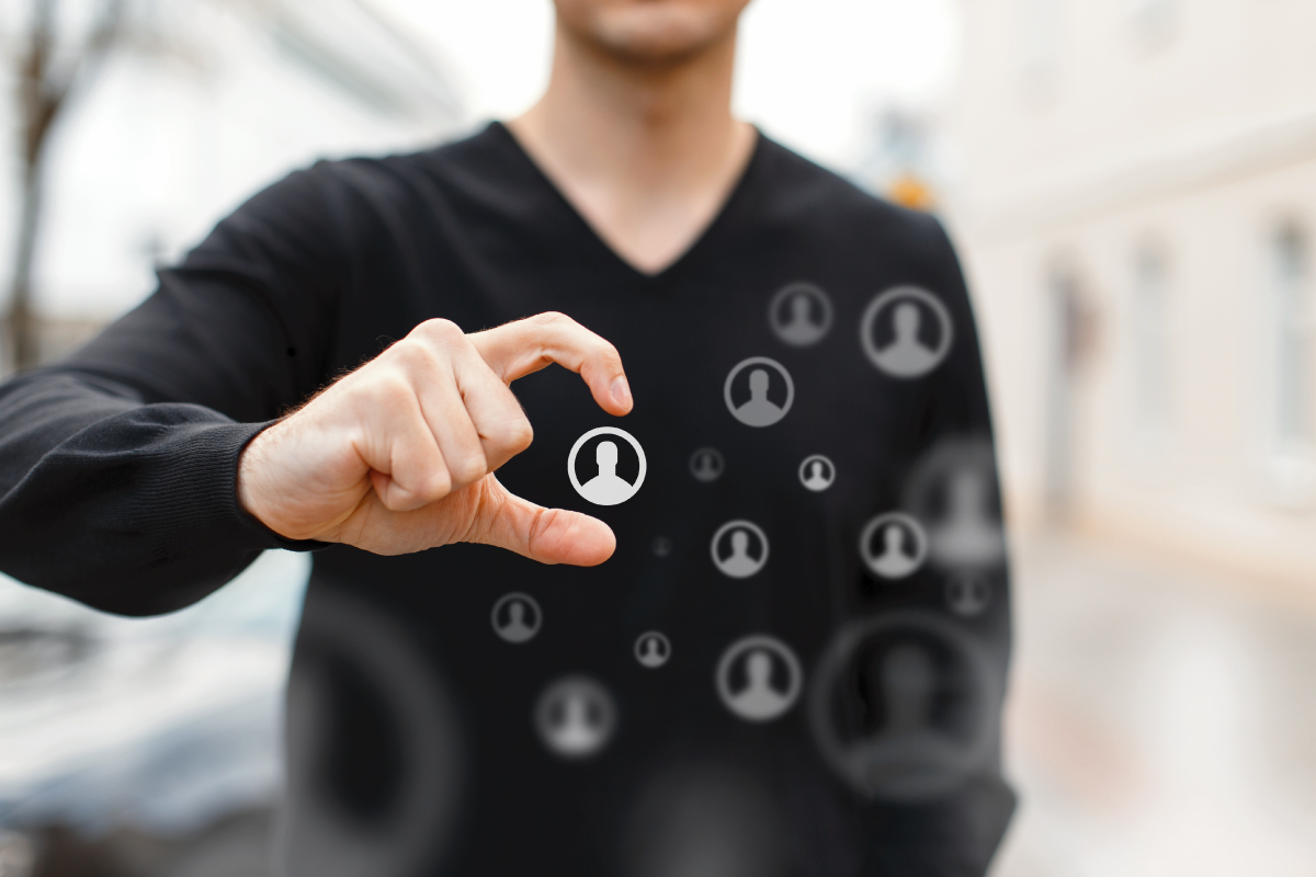 """Man holding fingers in a """"C"""" shape to select option among floating people icons"""